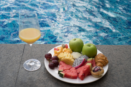 dragon swim: Fruit plate and glass of orange juice by hotel pool. Exotic summer diet. Tropical beach lifestyle.