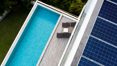Top view of outdoor swimming pool and solar panels on the roof of villa Stock Photo