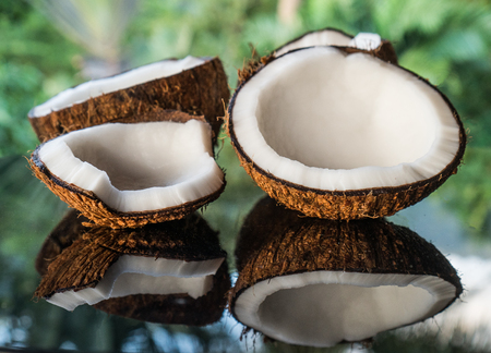 Closeup of coconuts on the black glass table isolated over blurred palm trees background Stock Photo