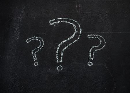 Three white question mark drawn with chalk on blackboard