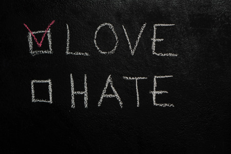 Love or Hate written with white chalk on blackboard Stock Photo