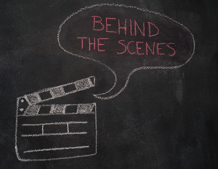 Open movie clapper and speech bubble with behind the scenes writing drawn with chalk on blackboard