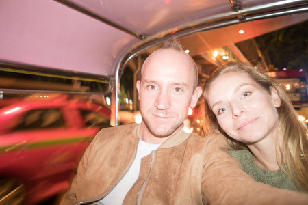 Pretty happy couple making selfie photo in tuk-tuk thai taxi during their holiday