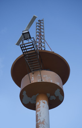 Bottom view of meteorological tower station over blue sky background