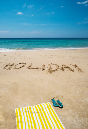 Holiday written on the beautiful sandy beach with towel and flip flops over blue sea and sky background