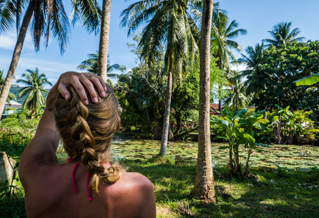 pozo de agua: Back view of woman looking at palm trees and dense tropical vegetation growing around small pond Foto de archivo