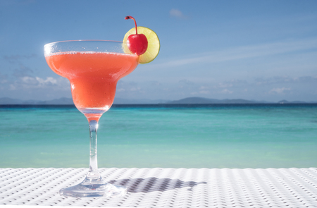open windows: Strawberry Daiquiri cocktail on the white rattan table at the beach restaurant with beautiful blue sea and sky background Stock Photo
