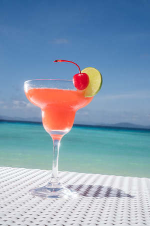 daiquiri alcohol: Strawberry Daiquiri cocktail on the white rattan table at the beach restaurant with beautiful blue sea and sky background Stock Photo
