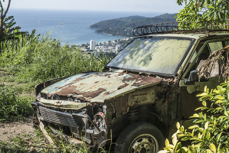 Rusty car abandoned on the hill isolated over beautiful tropical island lanscape background