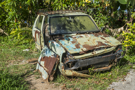 Rusty car abandoned near tropical palm trees