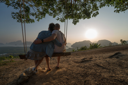 Couple sitting on the swinging bench over beautiful tropical mountain landscape during sunrise Stock Photo