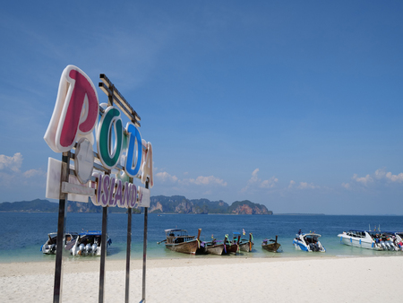 Colorful Poda island sign on the sandy beach over blue sea and sky background Editorial