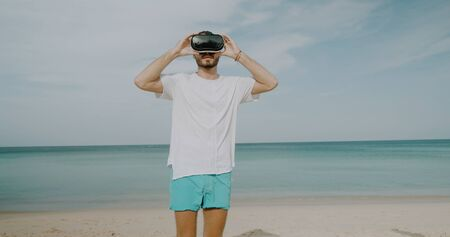 Young man using virtual reality glasses on the tropical beach over beautiful sea and sky background Reklamní fotografie
