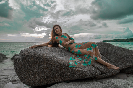 Beautiful mysterious woman in long dress laying down on the rock over sea and cloudy sunset sky background Stok Fotoğraf