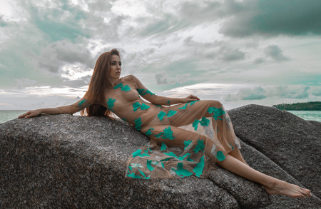 Beautiful mysterious woman in long dress laying down on the rock over sea and cloudy sunset sky background Stock Photo