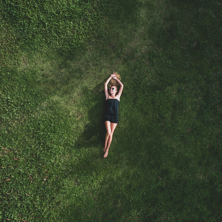 Aerial top view of happy woman relaxing on the grass during sunny summer day