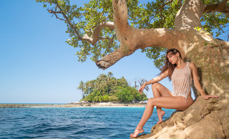 Beautiful  sensual woman sitting on the tree branch over tropical island, blue sea water and summer sky background Reklamní fotografie