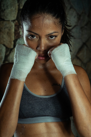 Sexy brunette fitness wet woman at the gym. Portrait of attractive woman in sportswear posing in combat stance with warpped hands