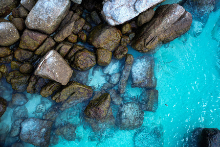 Aerial drone top view of crystal clear lagoon sea water surface with rocks and sun rays