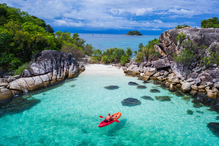 Aerial drone view of man kayaking in crystal clear lagoon sea water during summer day near Koh Kra island in Thailand. Travel tropical island holiday concept