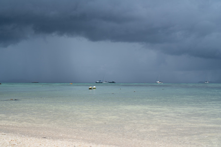 Sandy beach and sea with boats over cloudy sky. Koh Lipe island in Thailand