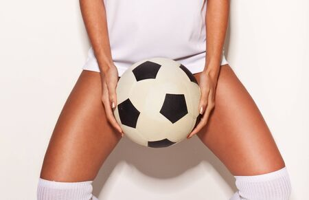 Closeup of female soccer player. Woman in white t-shirt and knee socks holding ball between legs over white wall background