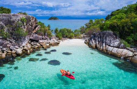 Aerial drone view of in kayak in crystal clear lagoon sea water during summer day near Koh Lipe island in Thailand. Travel tropical island holiday concept Stock Photo