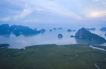 Aerial drone view of scenic tropical bay with limestone cliffs and rock formations during beautiful sunset