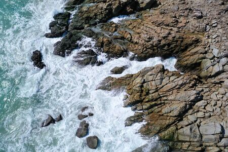 Aerial drone view of ocean's beautiful waves crashing on the rocky island coast