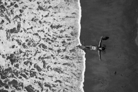 Black and white photo - aerial top view of woman with her hands outstretched laying on the sandy beach near the ocean. Summer holiday concept