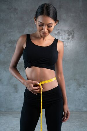 Portrait of fitness beautiful and smiling female model with measuring tape posing at the fitness gym