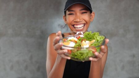 Portrait of beautiful young smiling woman in black t-shirt holding bowl with healthy salad over concrete background