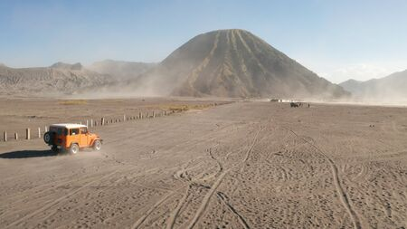 Cinematic shot aerial drone view of tour jeep cruise at beautiful Mount Bromo volcano with desert in East Java, Indonesia Фото со стока