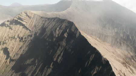 Cinematic drone shot aerial view of Mount Bromo crater edge with active volcano smoke in East Java, Indonesia