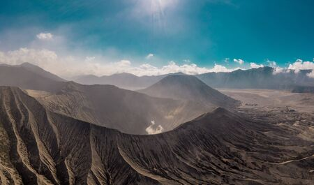 Cinematic shot aerial view of Mount Bromo crater with active volcano smoke in East Java, Indonesia
