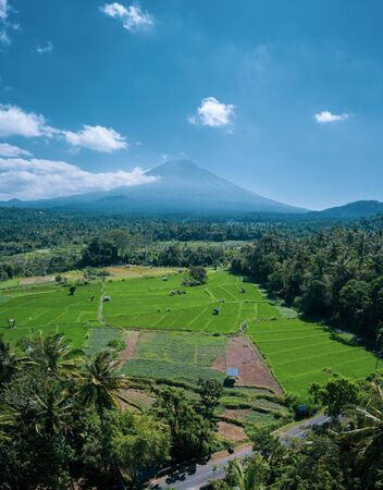 Aerial drone view of volcano and beautiful fields landscape during sunny summer day in Bali, Indonesia