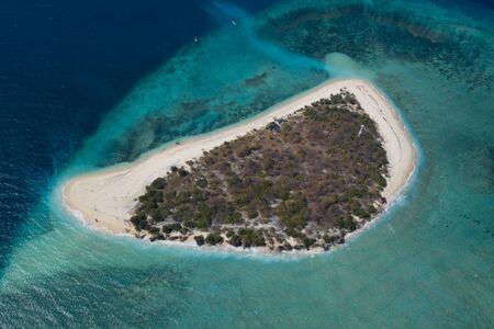 Aerial drone view of small exotic island surrounded by coral reef and blue sea Фото со стока