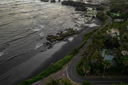 Aerial drone view of tropical island with black beach in Bali, Indonesia Фото со стока