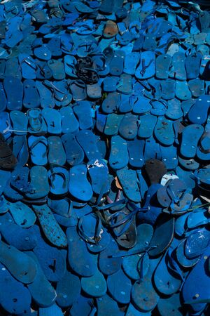 Recycled blue flipflops background.  Nature, environment, ecology concept Фото со стока