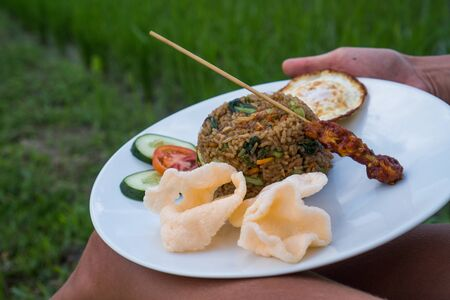 Nasi goreng, traditional Indonesian dish served with prawn crackers and chicken satay on white plate. Closeup womans hands holding plate with fried rice while sitting near rice fields