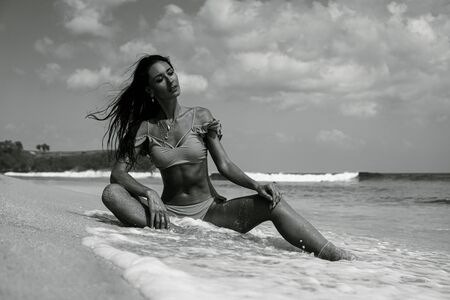Beautiful fitness woman in bikini posing at the beach - black and white photography