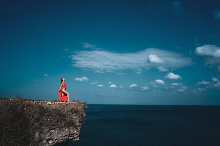 Aerial drone view of beautiful woman in red dress standing on the sea shore cliff during sunny summer day