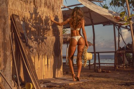 Back view of beautiful tanned fitness woman in bikini posing with straw hat near the beach