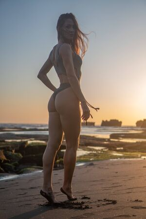 Back view of beautiful sensual woman in sparkling swimsuit posing at the black sand beach during amazing golden sunset