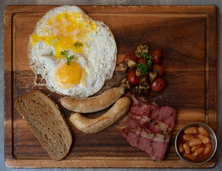 Top view of full cooked English breakfast on a wooden tray