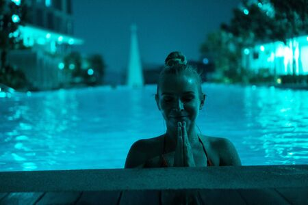 Woman in outdoor swimming pool with blurred city view at night