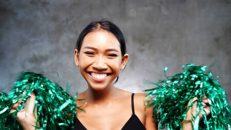 Portrait of beautiful young smiling girl with green cheerleader pom-poms over concrete wall background