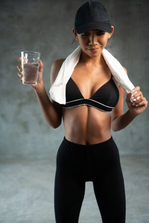 Portrait of fitness smiling model with towel holding protein idrink n the gym. Close-up of healthy woman with chocolate powder milkshake smoothie after sport workout