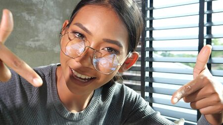 Portrait of young smiling woman vlogger pointing fingers down to like or subscribe her channel while recording her daily video blog. People, freelance work, comfortable lifestyle and technology concept