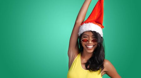 Studio bright summer portrait of beautiful smiling woman in yellow swimsuit and red sunglasses wearing Santa Claus hat isolated over green background